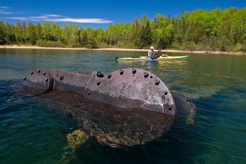 A sea kayaker explores an old shipwreck in Gargantua Harbor in Lake Superior Provincial Park near Wawa Ontario Canada.