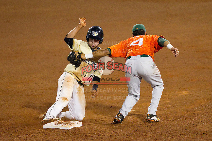 Miami Hurricanes second baseman Stephen Perez #4 tags out Pat Blair #11 as he tries to steal second base at NewBridge Bank Park on May 25, 2012 in Winston-Salem, North Carolina.  The Hurricanes defeated the Demon Deacons 6-3.  (Brian Westerholt/Four Seam Images)