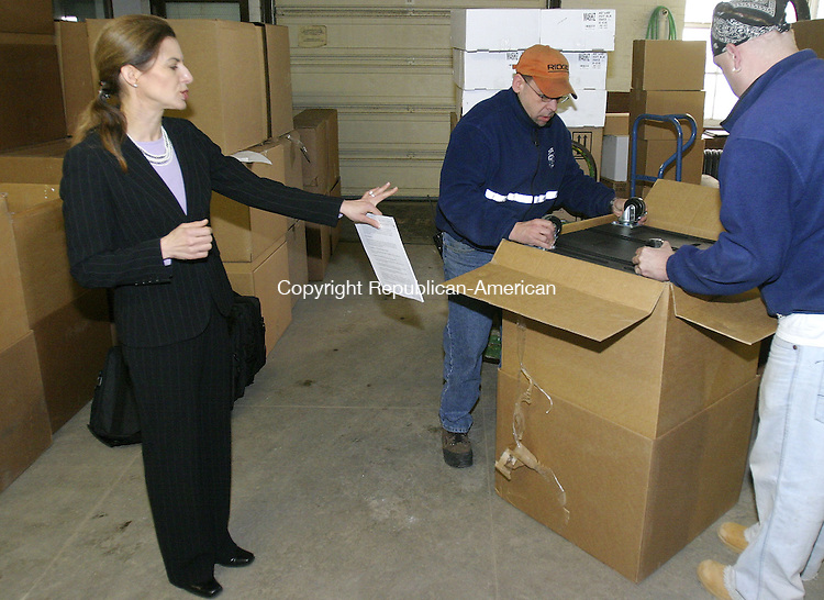 WATERBURY, CT. 08 March 2007--04_NEW_030807SV01--From left, Secretary of the State Susan Bysiewicz watches Bob Gaetano and Mike Geary unwrap one of the new voting machines Waterbury received at the Chase building on Thursday. The Secretary of the State&rsquo;s office is coordinating delivery this year of new voting machines to more than 140 towns and cities across Connecticut. Waterbury was receiving one of the larger shipments, 47 optical scanners. Most of Connecticut&rsquo;s communities still do not have this new technology in place but will receive shipment by the end of April.<br /> Steven Valenti Republican-American