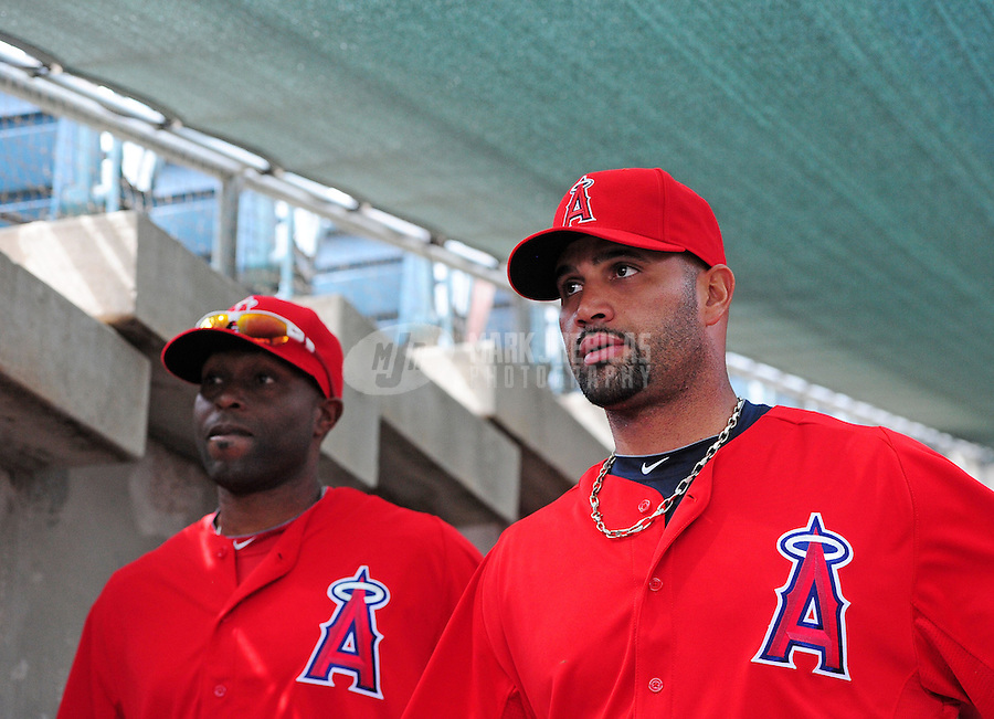 Mar. 4, 2012; Phoenix, AZ, USA; Los Angeles Angels first baseman Albert Pujols (right) and outfielder Torii Hunter walk to the dugout prior to the game against the Oakland Athletics during a spring training game at Phoenix Municipal Stadium.  Mandatory Credit: Mark J. Rebilas-