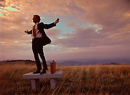 A businessman feels a sense of freedom while standing with his arms up in the air on a bench in a mountain field