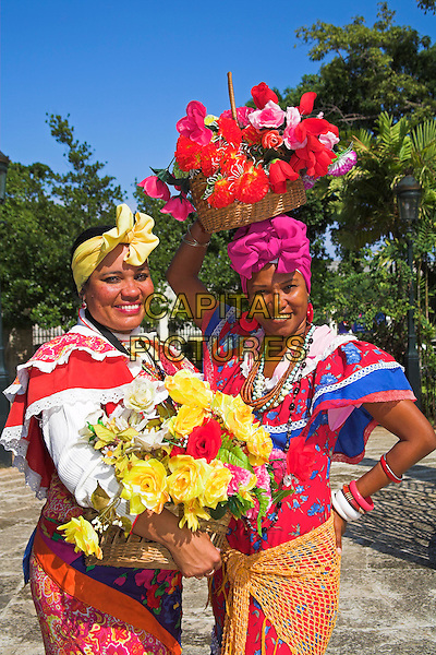 Two women wearing colourful traditional clothing, Plaza de Armas, Havana, La Habana Vieja, Cuba