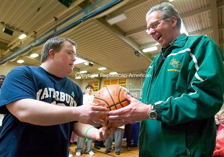 WATERBURY, CT--24 MARCH 2007--032407JS12-Event Director Ed Generali, right, is presented with a basketball by Team Waterbury's Michael Lovetro  during opening ceremonies at the Special Olympics Connecticut-Northwest Region's 2007 Traditional Basketball Invitational held at Holy Cross High School in Waterbury. The tournamnet was held at a total of five schools in the city of Waterbury.