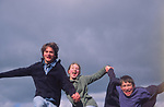 ADFRW2 Three teenage children running holding hands viewed from below looking up