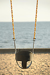 Toddlers swing with Long Island Sound background.