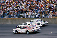 Neil Bonnett (21),Cale Yarborough and Darrell Waltrip in a 1979 NASCAR race at Michigan International Speedway near Brooklyn, Michigan.