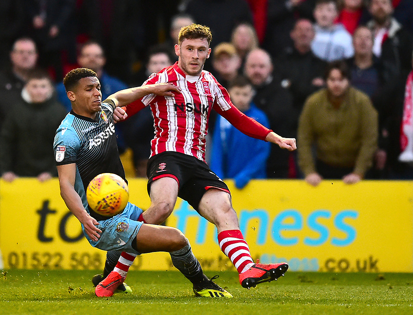 Lincoln City's Shay McCartan vies for possession with Stevenage's Luther Wildin<br /> <br /> Photographer Andrew Vaughan/CameraSport<br /> <br /> The EFL Sky Bet League Two - Lincoln City v Stevenage - Saturday 16th February 2019 - Sincil Bank - Lincoln<br /> <br /> World Copyright © 2019 CameraSport. All rights reserved. 43 Linden Ave. Countesthorpe. Leicester. England. LE8 5PG - Tel: +44 (0) 116 277 4147 - admin@camerasport.com - www.camerasport.com