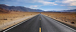 A Desert Highway And Distant Mountains In Death Valley National Park, California, USA