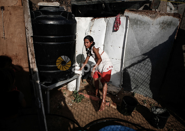 A Palestinian girl washes her hands from a water container outside her family's home in a poverty-stricken quarter of al-Zaytoon in Gaza City on Sept. 17, 2013. Reports said that an increasing number of Gaza families are reportedly falling further into poverty, with unemployment rate standing at over 30 percent and  poverty level of 39 percent according to 2013 estimates. Photo by Ezz Zanoun
