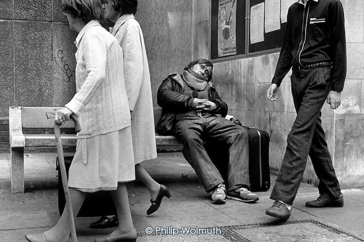 Pedestrians pass by a homeless man sleeping on a bench in Kings Cross, London.