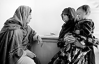 An ethnic Hazara woman with her child consult a doctor in the hospital in Jaghori, Afghanistan on Thursday,  June 20, 2002. She is one of thousands of Hazara refugees who have returned to Afghanistan from Iran to try to rebuild their lives. More than six million people fled Afghanistan during the years of conflict following the Soviet invasion in 1979.