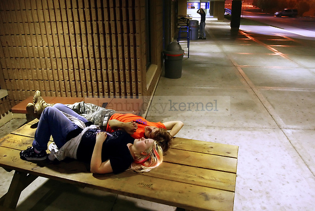 Dylan Parks, 14, and his girlfriend of nine months Angelica Moore, 15, cuddle in private on top of a pick-nick table outside of Pike County Central High School after the football game.  ..