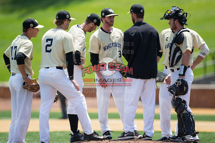 Wake Forest Demon Deacons assistant coach Matt Hobbs has a meeting on the mound with starting pitcher Connor Johnstone (3), catcher Ben Breazeale (39) and the entire infield during the game against the Pitt Panthers at David F. Couch Ballpark on May 20, 2017 in Winston-Salem, North Carolina. The Demon Deacons defeated the Panthers 14-4.  (Brian Westerholt/Four Seam Images)