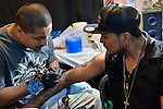 Garden City, New York, USA. September 13, 2015. GABINO SORIANO, a tattoo artist from Hammond, Indiana, tattoos a young man's arm at the United Ink Flight 915 Tattoo convention at the Cradle of Aviation Museum in Long Island.