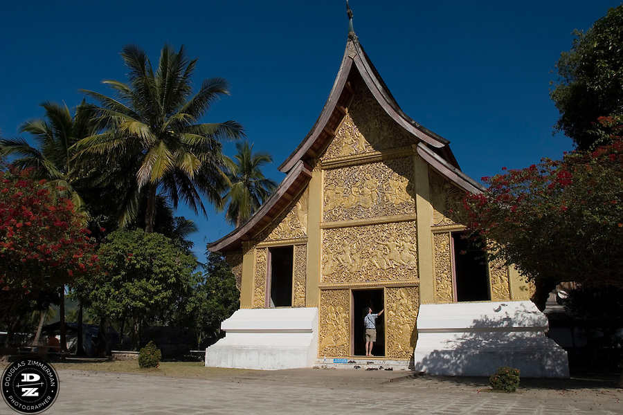 A tourist views one of the buddhist temples at Haw Kham (Royal Palace) complex in Luang Prabang, Laos. Photograph by Douglas ZImmerman.