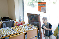 A young boy takes a look at freshly baked pastries prepared during an Oriental pastry workshop held by the non-profit association Batisseusses de Paix (or Women Peace Builders) that seeks to build ties between Muslim and Jewish women, in a restaurant in Creteil, outside Paris, France, 24 June 2008.