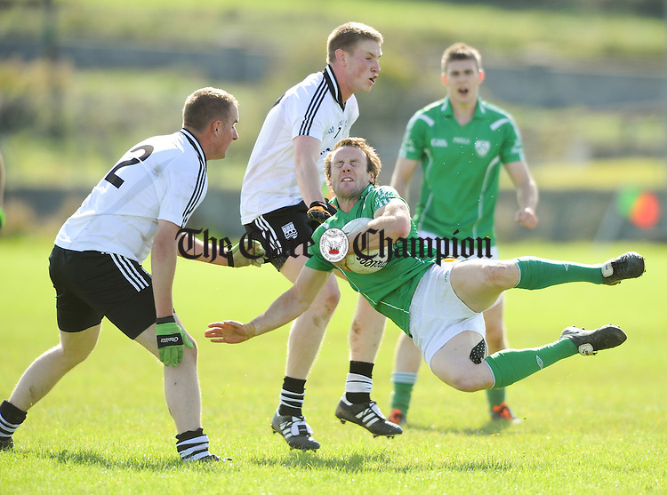 John Hayes of Kilrush goes flying in action against David Murphy and Michael Mc Donagh of Ennistymon  during their senior championship game at Quilty. Photograph by John Kelly.