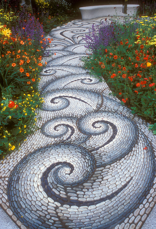 Stone Walkway In The Garden Leading To A Garden Bench, With Twists And  Twirls In