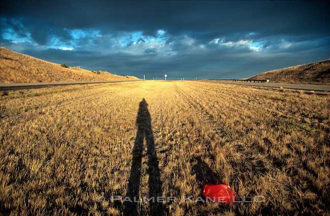Shadow of photographer next to Interstate highway with red plastic trash bag and approaching storm clouds