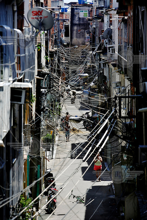 A mish-mash of electrical and telecommunications wires form a net above a street in the Favela da Mare.