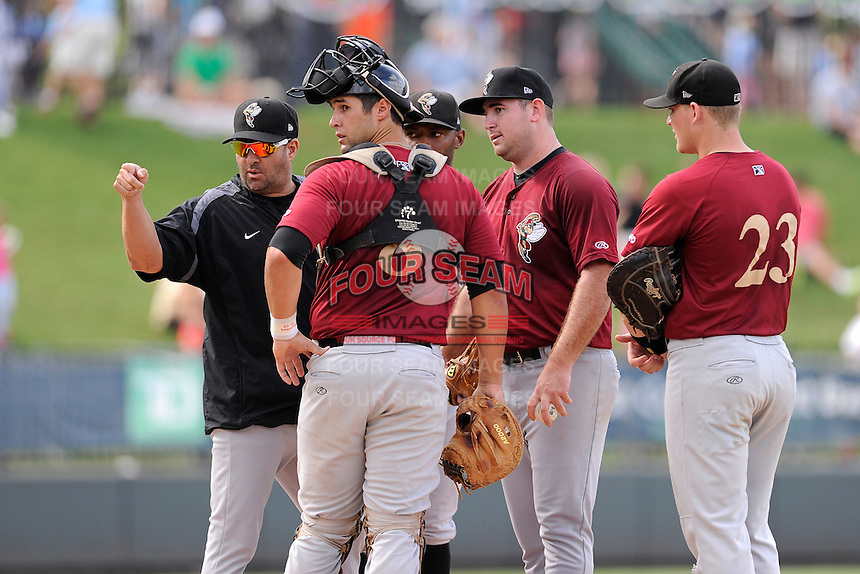 Pitching coach Marc Valdes (17) of the Savannah Sand Gnats, in the black pullover, points at umpire George Reidel during a game against the Greenville Drive on Sunday, August 24, 2014, at Fluor Field at the West End in Greenville, South Carolina. Valdes was ejected, and Greenville won, 8-5. (Tom Priddy/Four Seam Images)
