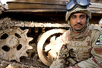 Iraqi tank commander Hadey Ali from the 1st company, 1st armour battalion of the 1st mechanized Iraqi Army Brigade seeks cover in back of his tank  while conducting  patrols, check points and observation posts on code name route Michigan, the main road of Ramadi in the week during the national election on WED Dec 14 2005 in Ramadi, Iraq. 1st company is part of the first armor battalion of the New Iraqi Army. it has started its training in January 2005. after 50 days their 35 russian and chinese built T 55 tanks begun conducting operations under the guidance of a US military adivisor team. in April 2005 they patrolled in the Abu Ghraib area concluding their first significant mission. While these old tanks are rolling on the ramadi streets more modern T72s are getting ready to become fully operational in Taji, their main base. the Iraqi army wanted to show their power in ramadi during the Dec 15 elections displaying their new armour company. but like all the other Iraqi forces they are not going to secure the polling sites, staying in the rear with the rest of the iraqi and coalition forces. T 55s are very old tanks. production begun in the late 50s to the late 70s. athough obsolete many countries still use the T55 as their main heavy armoured combat vehicle. slow, heavvy and with very little room for the crew it suffers from many mechanical problems constantly challenging the iraqi mechanics and engineers.