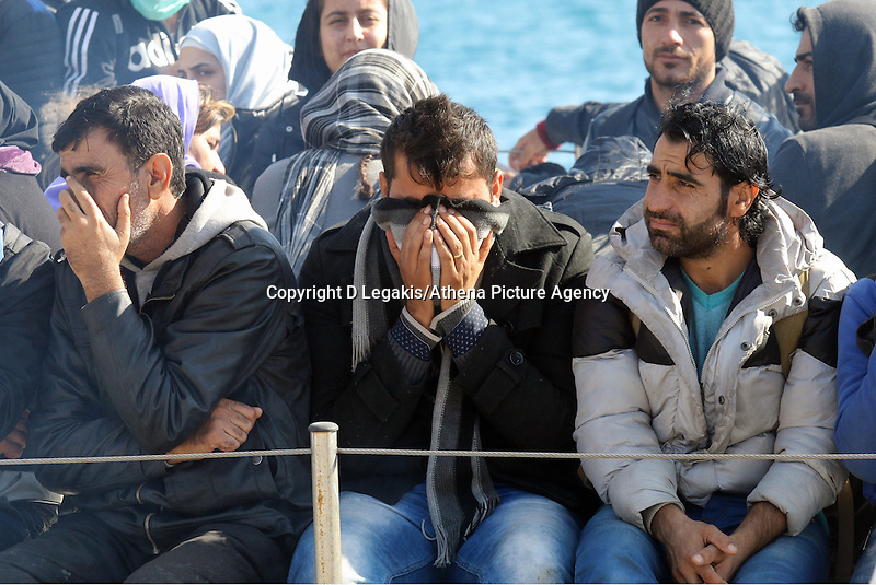 Pictured: Men hide their faces as they approach Ierapetra Thursday 27 November 2014<br /> Re: One of the largest refugee boats in recent months has disembarked refugees in Ierapetra, Crete. The freighter Baris, carrying 700 people thought to be from Syria and Afghanistan, is being towed by a Greek frigate.<br /> Officials and Red Cross volunteers prepared an indoor basketball stadium as interim shelter in the southern Cretan port town of Ierapetra on Wednesday ahead of the migrants' expected arrival.<br /> Greek officials said the Baris, which lost propulsion on Tuesday, was being towed slowly in poor sea conditions and would arrive after nightfall, probably early Thursday.<br /> They said it was unclear which Mediterranean location had been the departure point for the 77-meter (254-foot) vessel, which was sailing under the flag of the Pacific nation of Kiribati.