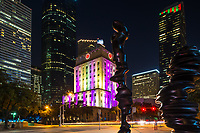 Colorful Houston City Hall at Night -  This colorful building is the Houston City Hall which lights up into a constantly changing light show.  We took this photo from across the street using the art statues at the Hobby Center to frame the shot.  Our biggest problem was deciding which color phase to use.