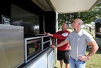 NWA Democrat-Gazette/DAVID GOTTSCHALK  Michael Bahn (left) reviews the operation of the satellite audio and video reception Friday, September 9, 2017, with Cory Rodney at their B'ville Hogs Squad tailgate area north of Donald W. Reynolds Razorback Stadium on campus in Fayetteville. The University of Arkansas plays Texas Christian University today at the stadium beginning at 2:30 p.m.
