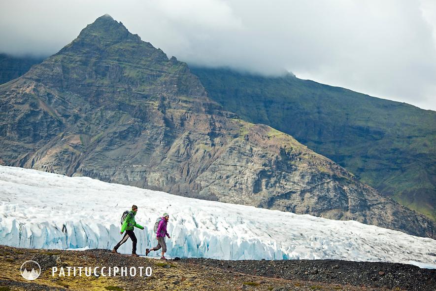 Couple hiking at the Fjallsarlon Glacier Lagoon, part of the National Park Vatnajokull