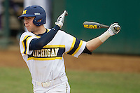 Michigan Wolverines second baseman Ramsey Romano (4) follows through on his swing during the NCAA baseball game against the Washington Huskies on February 16, 2014 at Bobcat Ballpark in San Marcos, Texas. The game went eight innings, before travel curfew ended the contest in a 7-7 tie. (Andrew Woolley/Four Seam Images)