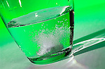 Tablet dissolves in a glass of water against a green background. Royalty Free
