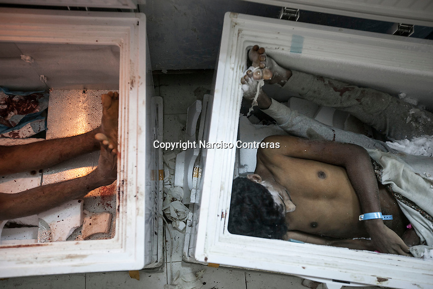 July 05, 2015 - Hajjah, Yemen: The bodies of three civilian lay at the morgue of  Jamhoony hospital in Hajjah city after he arrived from Harad, a border town where a fighter jet of the Saudi-led coalition dropped a bomb over a market place killing 30 and leaving 67 severely wounded. (Photo/Narciso Contreras)
