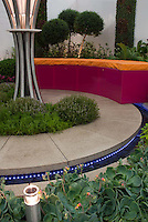 Circular patio with garden bench, fragrant plants, lighting, string lights, perennials, flowers