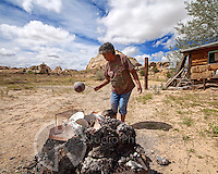 Rebecca Lucario Acoma Master Potter removing freshly fired vessel from the fire