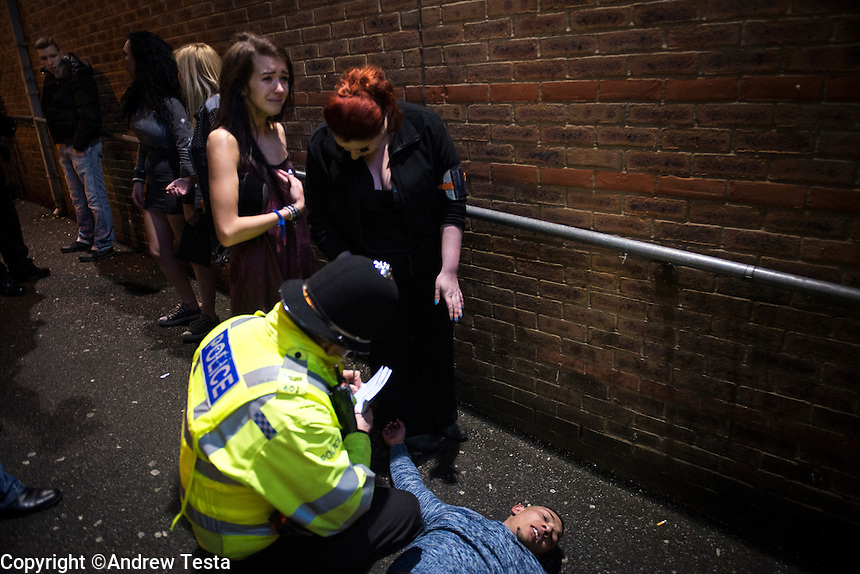 UK. Northampton. 7th December 2013<br /> An injured man lies on the floor after a fight in a northampton backstreet.<br /> &copy;Andrew Testa for the New York Times