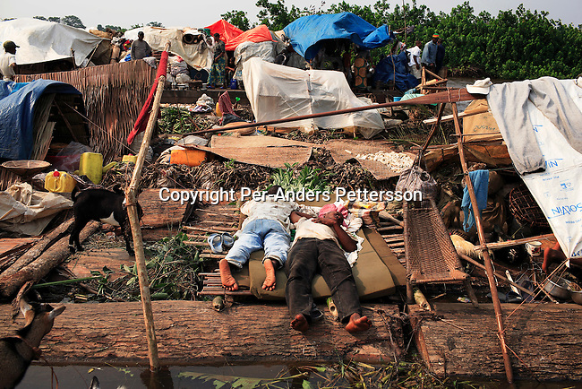 MBANDAKA, DEMOCRATIC REPUBLIC OF CONGO JUNE 26: Unidentified men sleep on a mattress while travel on a boat made of big trees on the Congo River on June 26, 2006 outside Mbandaka, Congo, DRC. The boat traveled with about 150 passengers from Bumba to Kinshasa, a journey of about 1300 kilometers. The Congo River is a lifeline for millions of people, who depend on it for transport and trade. Passengers slept in the open, with their goats, pigs and other animals. Boat travel is the only option for most people along the river as there?s no roads or infrastructure. Very few can afford to fly in a plane to the capital Kinshasa. During the Mobuto era, big boats run by the state company ONATRA dominated the river. These boats had cabins and restaurants etc. All the boats are now private and are mainly barges that transport goods. The crews sell tickets to passengers who travel in very bad conditions. The conditions on the boats often resemble conditions in a refugee camp. Congo is planning to hold general elections by July 2006, the first democratic elections in forty years. The Congolese and the international community are hoping that Congo will finally have piece and the country will be rebuilt..(Photo by Per-Anders Pettersson/Getty Images)...