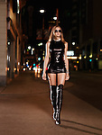 Attractive young blond woman in a sexy outfit and high boots walking down a city street at night. Yonge Street, downtown Toronto, Ontario, Canada.