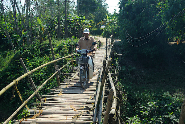 Asia, Vietnam, Hue. Vietnamese man on small motorbike crossing a toll-bridge. Designated a UNESCO World Heritage Site in 1993, Hue is honoured for its complex of historic monuments.