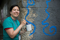 "Ali Grotkowski poses for a photo in front of a mural during ""Circle the City with Service,"" the Kiwanis Circle K International's 2015 Large Scale Service Project, on Wednesday, June 24, 2015, in Indianapolis. (Photo by James Brosher)"