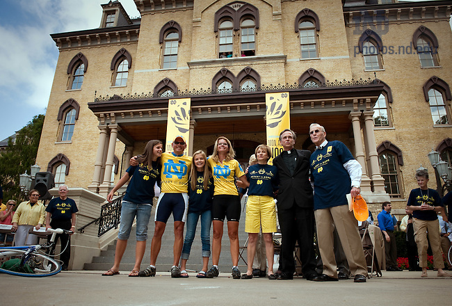 """College of Science Dean Greg Crawford, his wife Renate and their daughters sing the Alma Mater with Cindy Parseghian, President Rev. John Jenkins and Alumni Association director Chuck Lennon after a welcome home ceremony at the main building after their """"Desert to Dome"""" bike ride from Tucson, AZ to South Bend, IN to promote the Notre Dame-Parseghian Foundation partnership...Photo by Matt Cashore/University of Notre Dame"""
