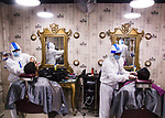 Pictured:   Barbers dressed in protective suits and face masks trim hair as businesses reopen in Dhaka, Bangladesh.<br /> <br /> The country's government has announced that certain businesses including large shops, malls and hair salons could reopen to restart the economy, following the COVID-19 outbreak.<br /> <br /> Please byline: Sultan Ahmed Niloy/Solent News<br /> <br /> © Sultan Ahmed Niloy/Solent News & Photo Agency<br /> UK +44 (0) 2380 458800