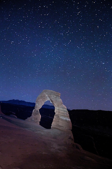 The night sky comes alive beyond Delicate Arch at Arches National Park, Utah