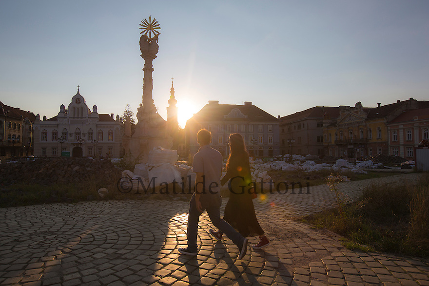 Romania - Timisoara - A young couple walks by Piața Unirii (Unity Square) in the center of the city.