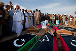 Residents of Al-Qala and Om Al-Jersan gather for the burial of eight bodies found last week in a mass grave near the town of Al-Qala in the Nefusa Moutains, Libya, Friday, Sept. 30, 2011. The eight were reburied next to 35 bodies found in a separate mass grave in the area. Members of the Amazigh indigenous tribe, the men were arrested from their homes and at checkpoints by pro-Gaddafi forces, imprisoned, and finally executed sometime in June. The men, many of them related as fathers and sons, or as brothers, were missing until the first, larger mass grave was found in mid-August.