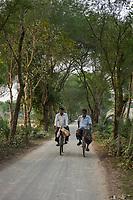 Bangladesh, Jhenaidah. People going down the road on bikes.