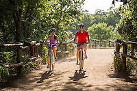 Active young couple riding bikes on Zilker Park Hike And Bike Trail on a beautiful summer's day in Austin, Texas.