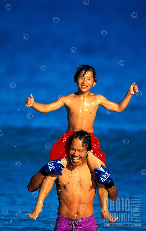 Father and son playing in the ocean
