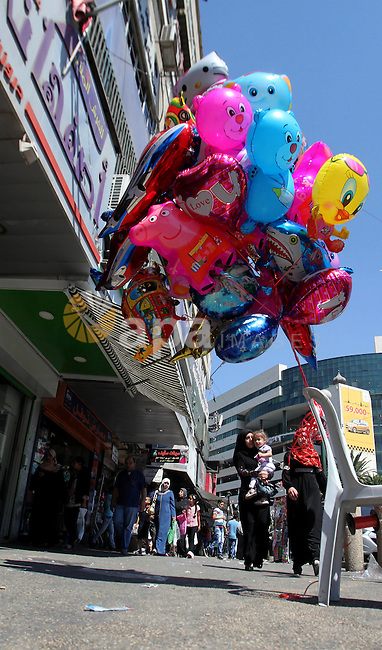 A Palestinian vendor sells ballons at a market ahead of the Eid al-Adha festival in the West Bank city of Nablus on Sept. 11, 2016. Photo by Nedal Eshtayah
