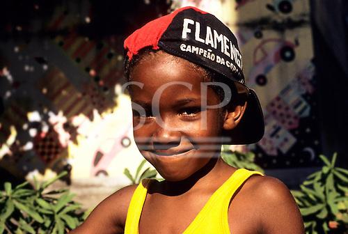 Rio de Janeiro, Brazil. Smiling young boy wearing a Flamengo football team hat and yellow sleeveless t-shirt.